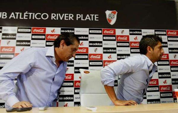 El DT de River y su hijo Emiliano se retiran raudamente de una rueda de prensa.