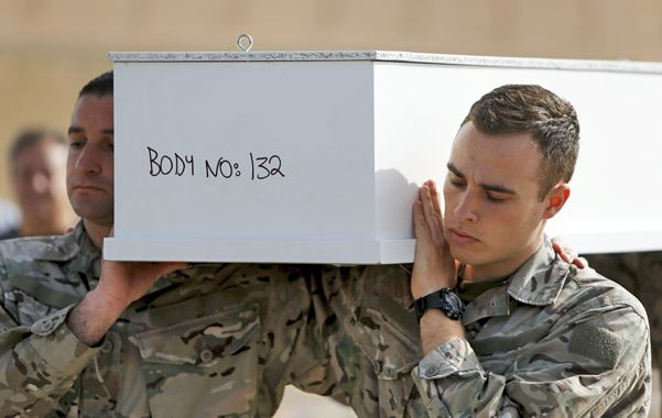 Cuerpo Número 132. Soldados de Malta trasladan el ataúd de un adolescente ahogado el pasado domingo.