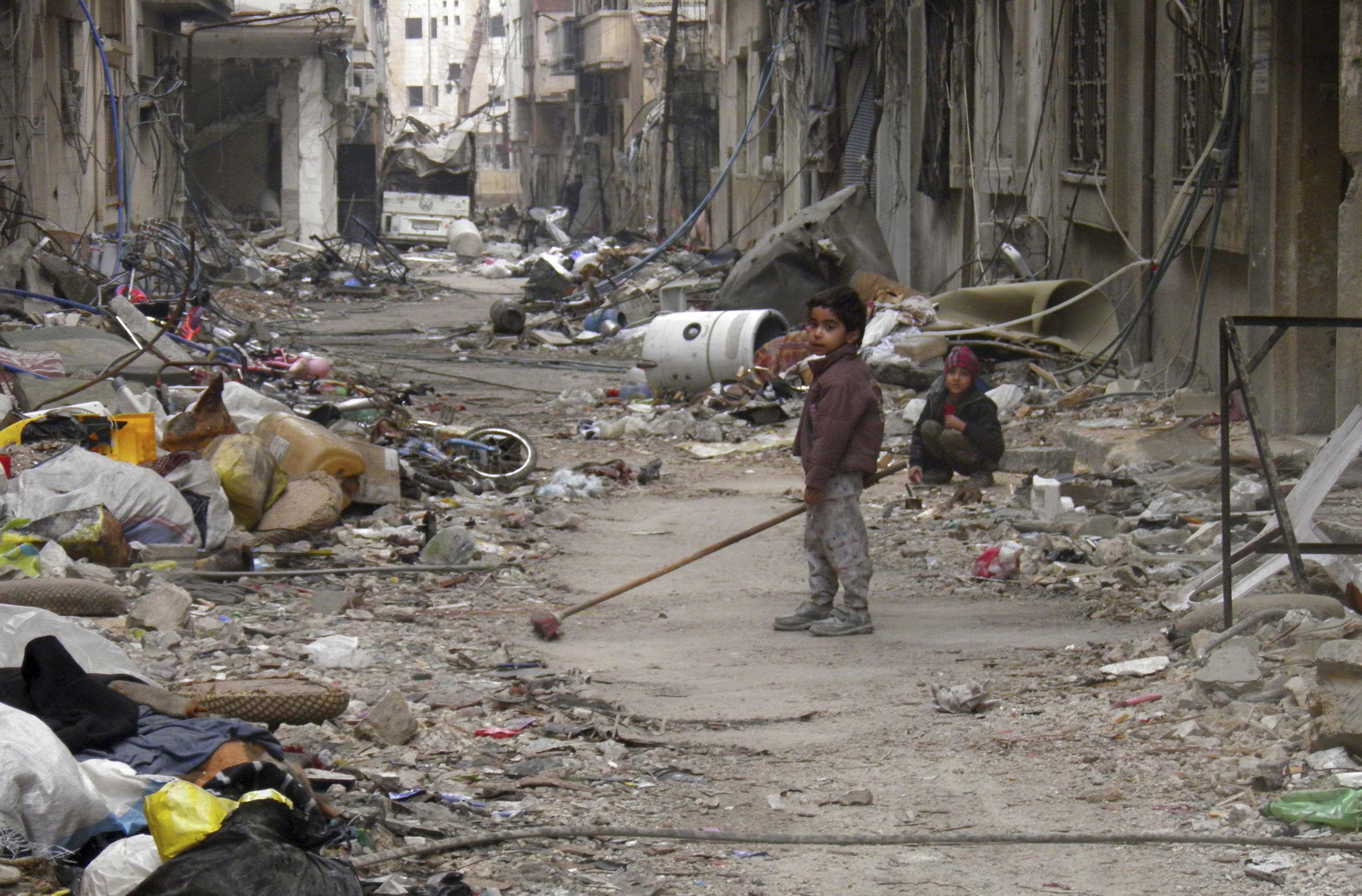 Dos chicos en las calles derruidas del centro de Homs