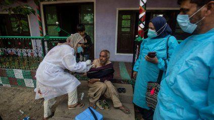EPIDEMIA. Agentes sanitarios de la India van a los barrios a vacunar con Covishield-AstraZeneca, elaborada allí.
