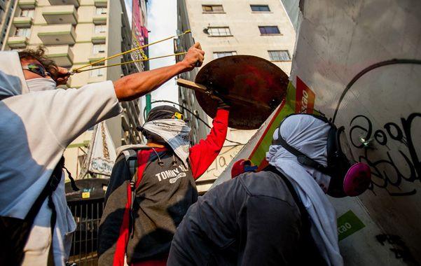 Agitación. Jóvenes con rostros cubiertos desafían a la policía en Caracas.