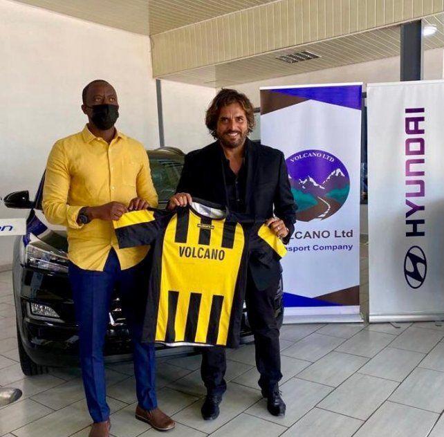 Rodolfo Zapata exhibe la camiseta de Mukura Victory junto al presidente del club aurinegro.