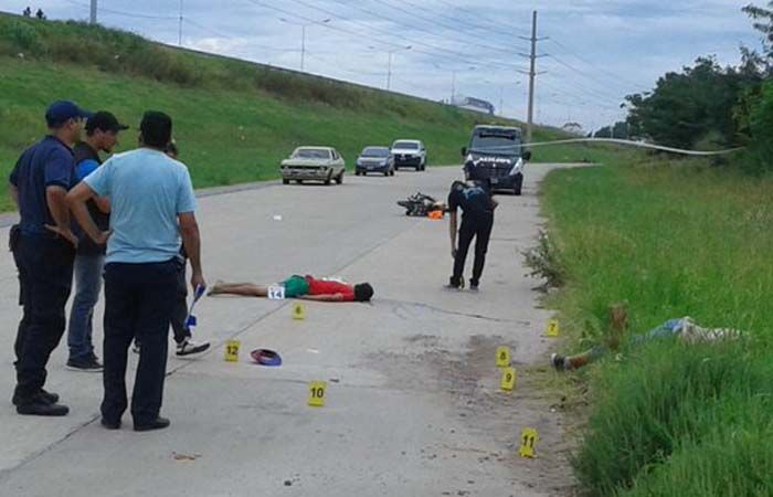 Los cuerpos de los chicos asesinados yacen en el piso. (Foto Twitter @EvelinMachain)
