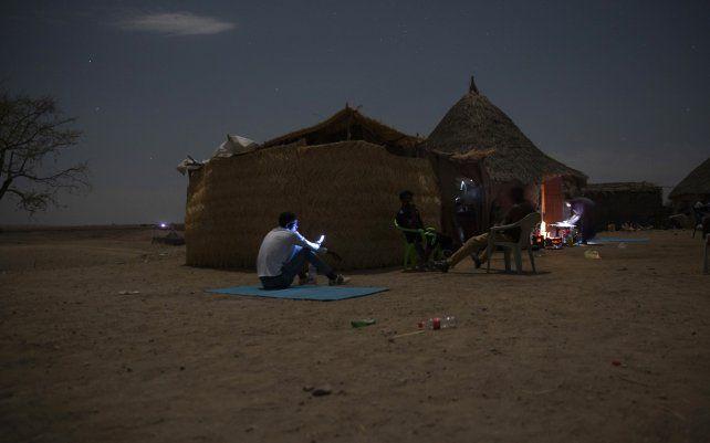 Refugiados de Tigray que huyeron del conflicto de Etiopía intentan encontrar una señal de red para sus teléfonos móviles en Hamdayet, en el este de Sudán, cerca de la frontera con Etiopía.