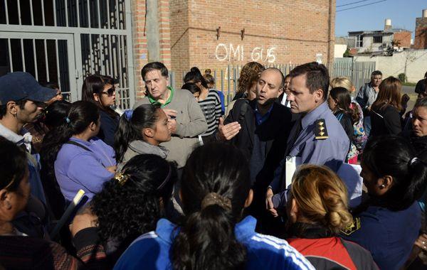 La madre que hizo la denuncia con personal policial en la puerta de la escuela. (foto: Enrique Rodríguez)