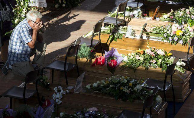 Sin consuelo. Un hombre se despide de un familiar en el estadio cubierto donde se realizó la ceremonia fúnebre.