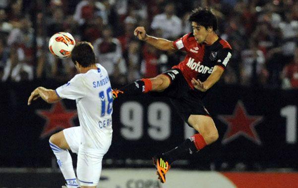 Pura lucha. Pablo Pérez salta para patear delante de Cerro.