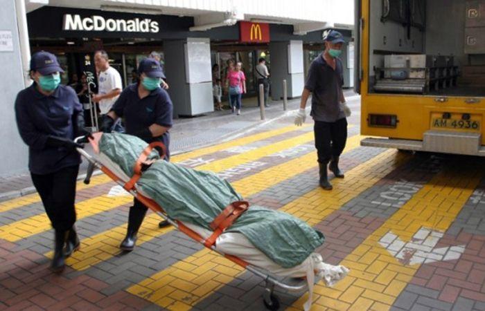 La mujer es retirada sin vida del local de comidas rápidas. (image: South China Morning Post)