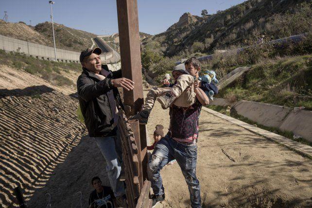 Migrantes cruzan con chicos el muro fronterizo entre Tijuana y San Diego.