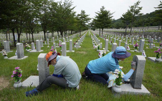 Trabajadores realizan mantenimiento a los epitafios en la lápida de los soldados que murieron durante la Guerra de Corea antes del 71° aniversario de la guerra el 25 de junio en el Cementerio Nacional de Seúl