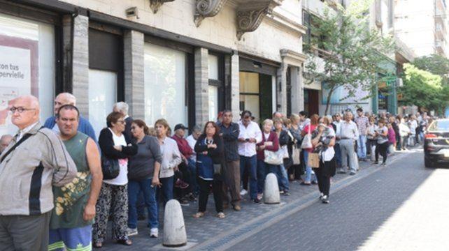 Grupos de riesgo. Una larga hilera de jubilados se formó ayer ante las puertas de una sucursal bancaria de Sarmiento y San Lorenzo.