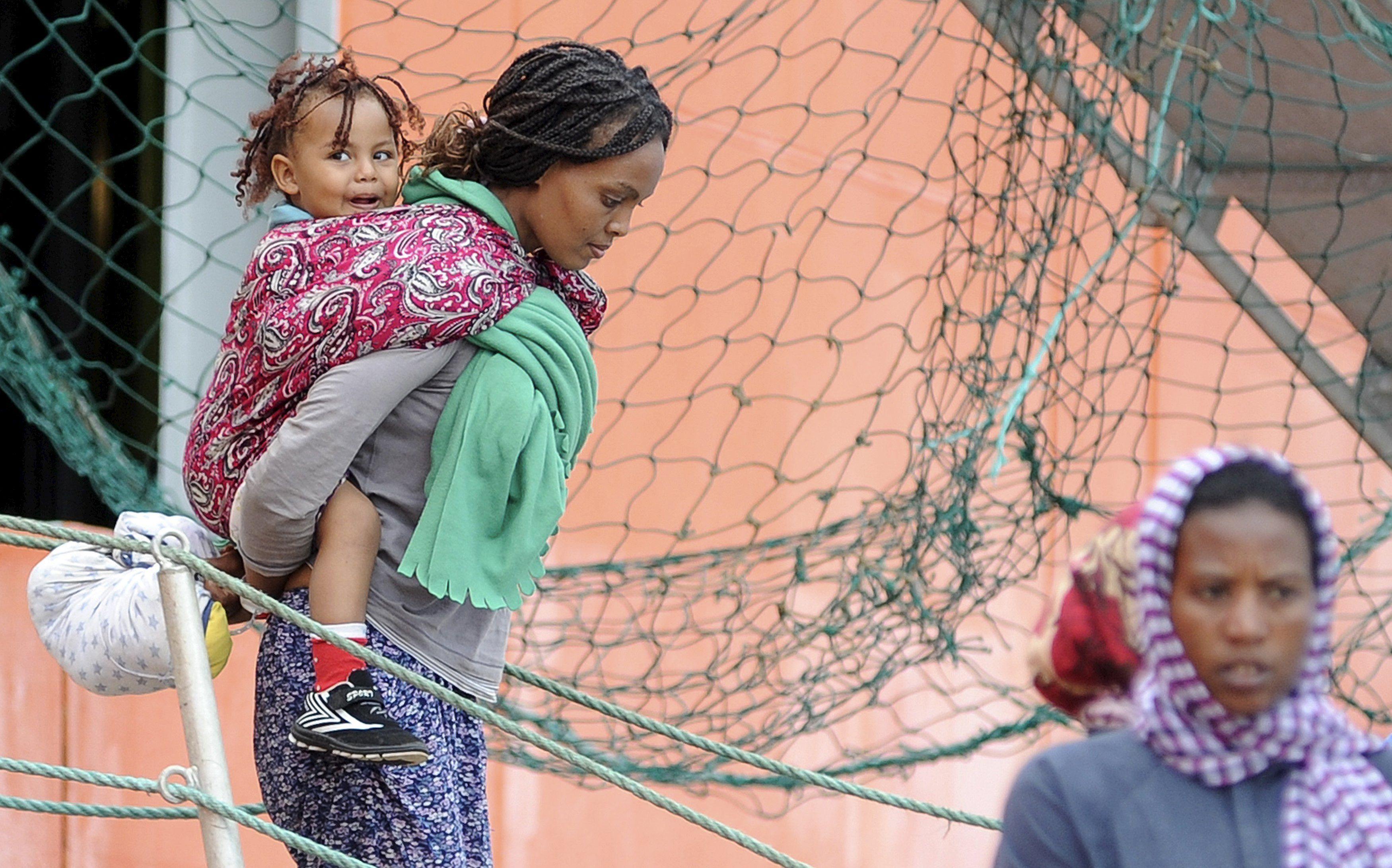 Arribo. Una migrante africana con su hija desembarca en Parlermo