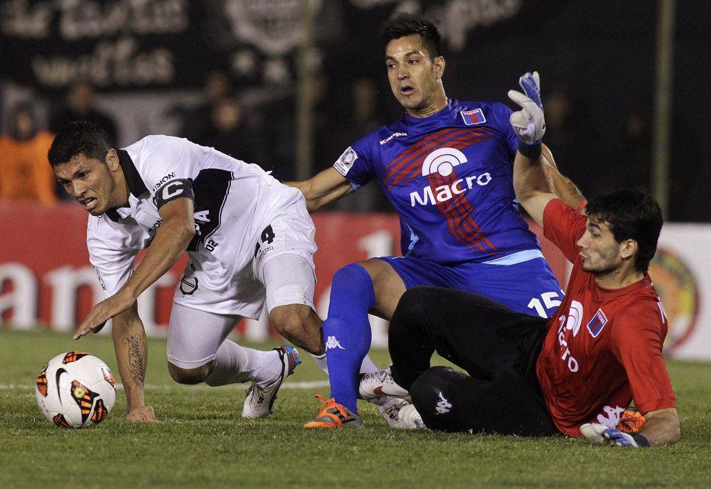 Por el piso. Aranda pasa entre Gastón Díaz y Javier García. El conjunto paraguayo inclinó la balanza en el complemento.