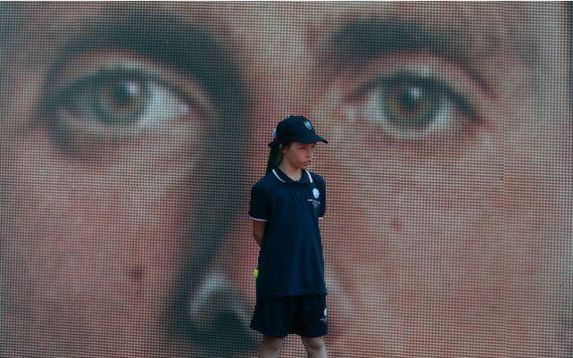 Una chica alcanza pelotas se para frente a una pantalla led que muestra a Novak Djokovic de Serbia antes de su partido de tenis del torneo de tenis abierto de Belgrado contra Mats Moraing de Alemania