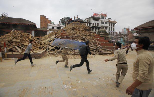 Devastador. Voluntarios corren para asistir a personas que quedaron atrapadas entre los escombros de edificios y templos de la ciudad de Katmandú.