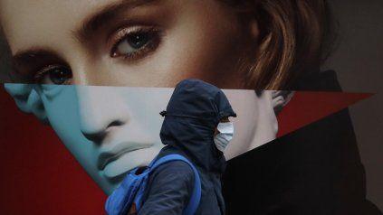 Un hombre con máscara facial pasa junto a un cartel publicitario en Londres, durante el tercer cierre nacional de Inglaterra para frenar la propagación del coronavirus.