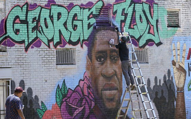 Un joven pinta un mural en honor a George Floyd