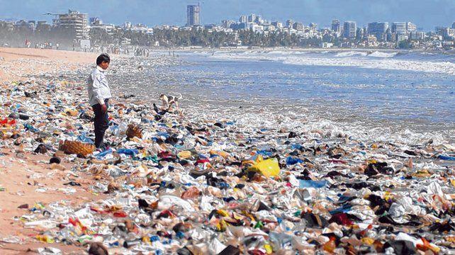 India. Un hombre detenido en medio de las sobras de alimentos y desechos plásticos en la costa de Bombay.