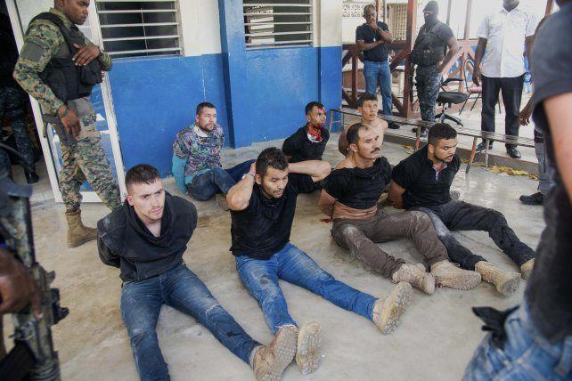 La policía haitiana exhibió a siete detenidos presuntos sospechosos del maginicidio Uno de ellos está herido y sangra profusamente.