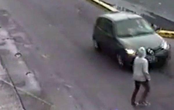 El instante antes de que la mujer se arroje encima del automóvil que circulaba por la avenida.