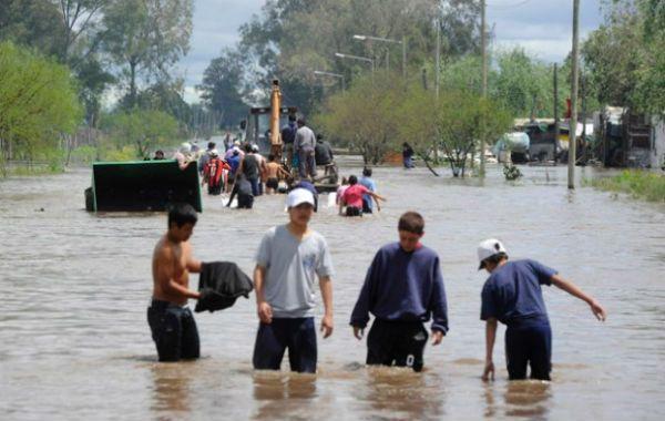 Los jóvenes caminan como pueden. Nuevo Alberdi fue uno de los barrios víctima del desborde de los canales.