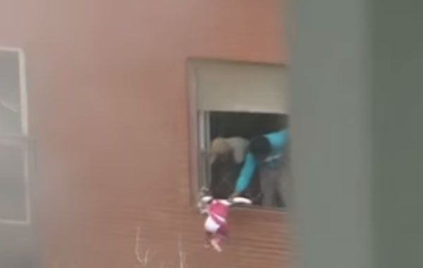 Los padres arrojan a la pequeña de tres años en un intento desesperado por salvarla de las llamas.
