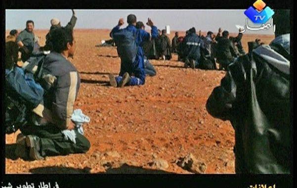 Un grupo de rehenes liberados argelinos levanta sus manos para no ser acribillado por las tropas.