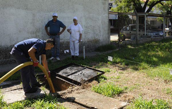 Un operario manipula una manguera desagotadora para desalojar el agua servida. (Foto: C. Mutti)