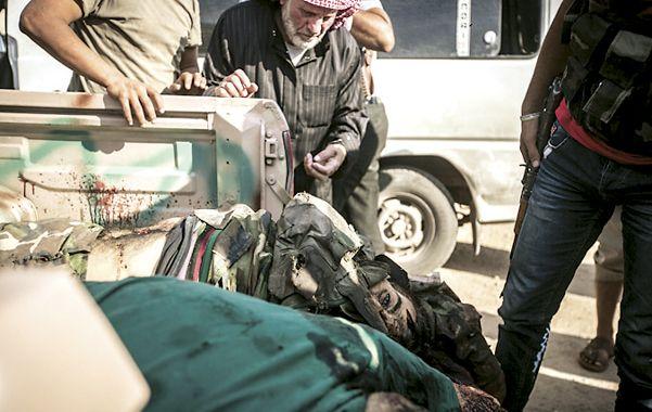 Sin fin. Los cuerpos de dos militares regulares yacen en una camioneta.