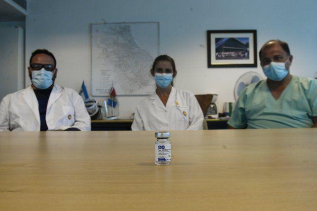 La dirección del Heca (Jorge Bitar, Andrea Becherucci y German Camiletti) posan detrás del primer frasco de vacuna que se colocó en el hospital.