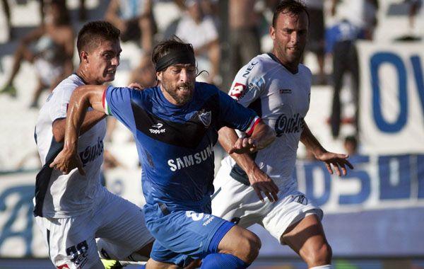 Pavone lucha entre dos jugadores de Quilmes. El Fortín no pudo con el local.