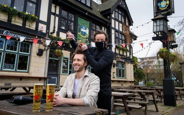 Un cliente recibe un corte de pelo gratis en una peluquería emergente. Millones de personas en Inglaterra tendrán su primera oportunidad en meses para cortarse el pelo