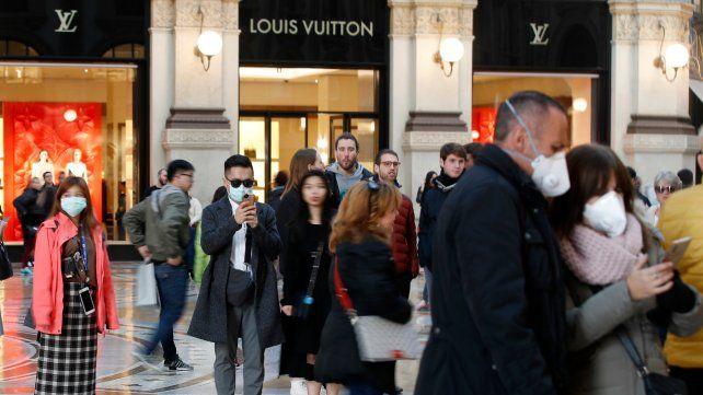 Turistas pasean por las calles de Milán con barbijos.