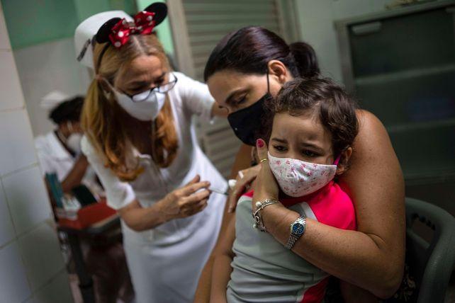 LA HABANA. Una mamá sostiene a su beba que recibe la primera dosis contra el coronavirus.