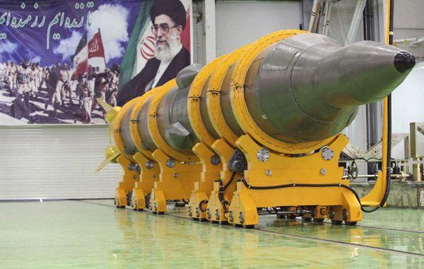 Un misil iraní de gran alcance Sejil-2 frente a un mural del ayatolá Alí Khamenei.