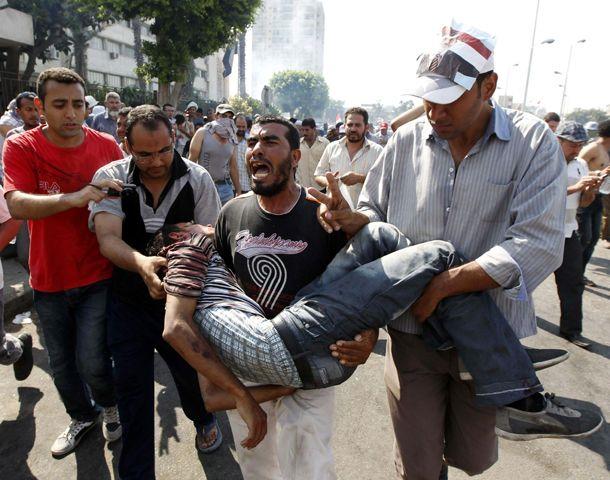 Un egipcio gravemente herido es trasladado por sus compañeros cerca de la plaza Tahrir.