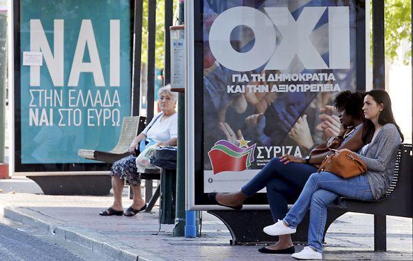 """Incertidumbre. Una parada de autobús en Atenas con pancartas pidiendo por el """"sí"""" o por el """"no"""" en la consulta."""