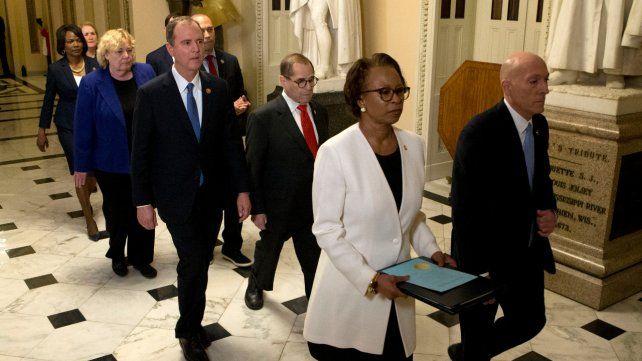 Solemnes. Funcionarios de protocolo portan el documento de la acusación desde la Cámara baja al Senado.