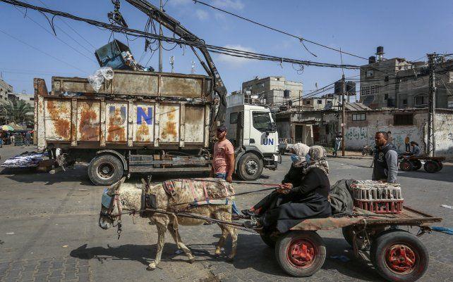 Mujeres palestinas montan un carro de burro frente a un camión de basura de la Agencia de Obras Públicas y Socorro de las Naciones Unidas (UNRWA) en el campo de refugiados de Rafah. El nuevo gobierno de Joe Biden, quiere reintroducir el apoyo a los palestinos detenido por el ex presidente Donald Trump.
