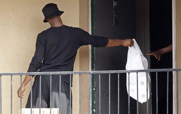 Dallas. Un hombre pasa una bolsa de la Cruz Roja y del Banco de Alimentos en el apartamento donde vive el enfermo.