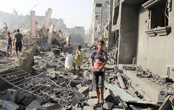 Destrucción. Un grupo de niños busca algo de valor entre los escombros en Rafah