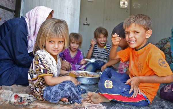Chicos shiítas que debieron escapar de Mosul comen en un campo de refugiados cerca de Bagdad.
