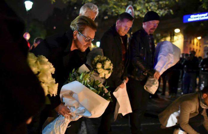 Los integrantes de la banda colocan flores ante el Bataclan.