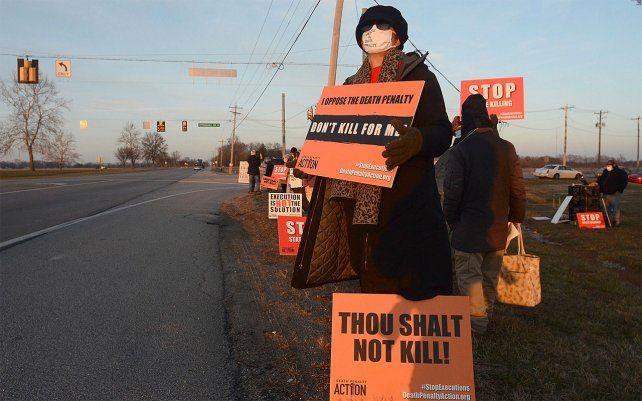 Una manifestante sostiene un cartel frente al Complejo Correccional Federal en Terre Haute, Indiana, para protestar por la ejecución programada de Lisa Montgomery.