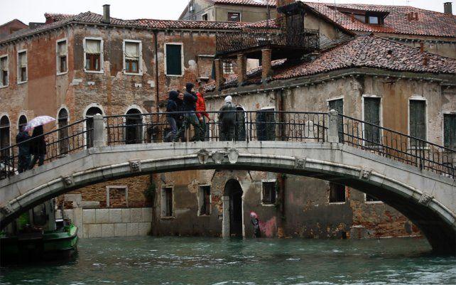 El mural de Banksy sobre un niño migrante, en la parte inferior central, parcialmente sumergido. La ciudad italiana de Venecia a solo tres días después de que experimentó su peor inundación en 50 años, noviembre de 2019.