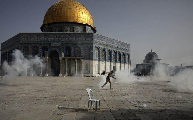 Un palestino huye de los gases lacrimógenos durante los enfrentamientos con las fuerzas de seguridad israelíes frente a la Mezquita de la Cúpula de la Roca en el recinto de la Mezquita Al Aqsa en la Ciudad Vieja de Jerusalén.
