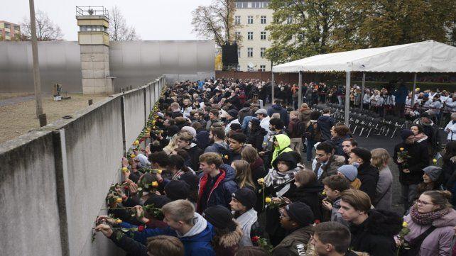 Los asistentes al acto presidido por Angela Merkel colocan rosas amarillas en los huecos del muro preservado.