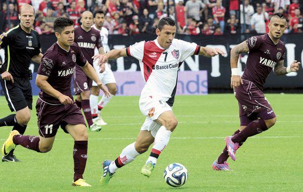 A paso firme. Maximiliano Rodríguez avanza con la pelota dominada entre los jugadores de Lanús pero su intento quedará en las manos del arquero Ibañez.
