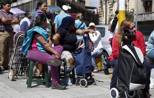Sentada. Armados de paciencia los venezolanos aguardan en fila frente a un centro de distribución de alimentos.