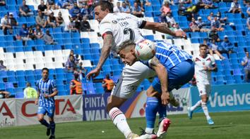 Lema disputa la pelota con Lomónaco. El zaguero se sumó al desconcierto general.